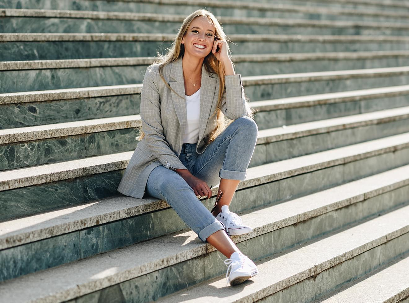 Image of a beautiful tan blonde woman sitting outdoors on stairs.